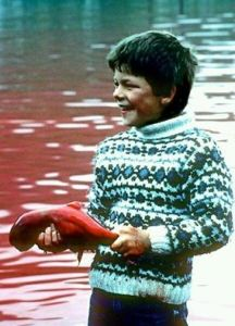 Photo-Boy holding a pilot whale featus from the Faroe islands killings that took place over the last few days...